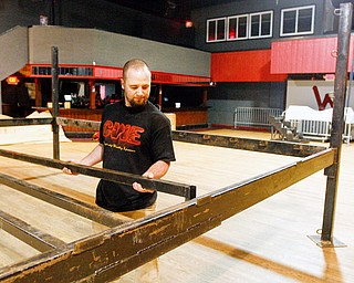 Kyle Terreri assembles the steel frame  for the wrestling ring at the Wedge in Austintown