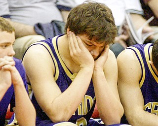 Sebring players, Jesse James, Joe George and Anthony Corbett sit quietly as their state title bid was ended by Marion Local in the semi finals. Sebring lost 52-45.