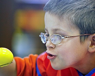 Bo Snyder takes an up close look at perfection as he dips his yellow egg in for more  coloring as  Preschoolers decorate Easter Eggs at New Life Christian Preschool, 2250 E. Western Reserve Road Poland