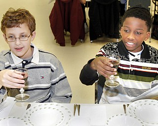 Korey Burdman, 13, of Howland and Maalik Smith, 11, a student at Akiva Academy participate in  a Seder at the Jewish Community Center Tuesday.The Seder was dedicated to child nutrition and hunger awareness.
