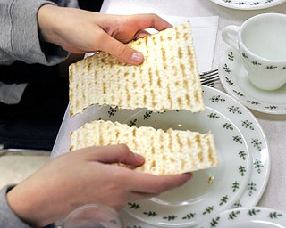 Breaking of Matzah. It is broken to remind people of the brokeness in the world and to recall those who are poor.  Rabbi Frank Muller ofCongregation Rodef Shalom lead a Seder at the Jewish Community Center Tuesday.The Seder was dedicated to child nutrition and hunger awareness.