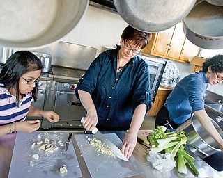 Deana Berman, 12 of Boardman, and Sherri Garver, of Columbiana County, peel garlic while Chaia Beckerman gets water for a stew being prepared at the Ohev Tzekek Synagogue in Youngstown on Wednesday. The stew is being prepared as part of a Passover meal.