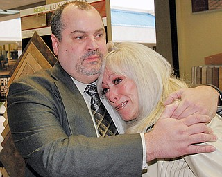 Carpet King general Mgr John Plesea hugs Cindy Barb, widow of Carpet King owner Ron Barb who died in March. She was emotional entering the store.