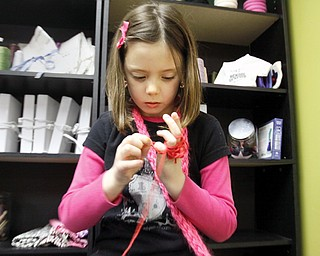 Cortney Prout (7) of Canfield demonstrates finger knitting at Design It in Canfield,