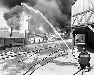 April 26, 1984; Lone firefighter fightsmidway fire.