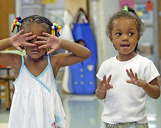 """Ariell Dorsey, 4, left, and Jada Baty, 3, sing a song during a class at the Mill Creek Children's Center summer session 07/09/08 in Youngstown. The center provides a variety of classes and services for children. According to its website its' mission is to provide young children of lower-income working parents with an excellent education and broad support services so that their lives can be enriched, productive and fulfilling."""" William D. Lewis"""