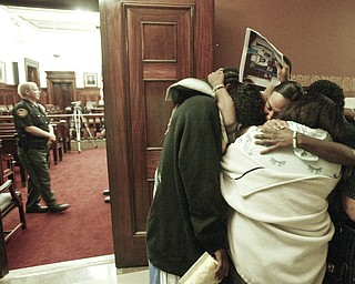 Retia Crawford, facing camera and other members of her family embrace outside a Mahoning County courtroom after Michael Davis found guilty of setting a fire that killed 6 members of the Crawford family. The Vindicator/William D. Lewis