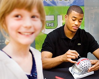 Former OSU Buckeye and future Cleveland Brown, Brian Robiskie signs a helmet for Meg Stein, 8, of Cortland during an autograph session at Eastwood Mall Saturday afternoon.