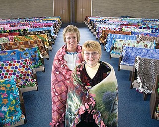 """BLESSED BLANKETS: Wanda Marland, foreground, and Diane Wise, coordinators of the Comfort Blanket Ministry at Western Reserve United Methodist Church in Canfield, are wrapped up in two of the 117 blankets made by church members as a special project. Blankets """"take their seats"""" in the sanctuary, where they were blessed."""