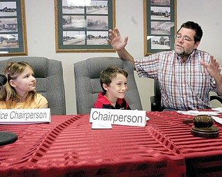 TEMPORARY TRUSTEES: Larry Wehr, a Beaver township trustee, explains the workings of township government to South Range third-graders Megan Kiselica and Cameron Tarr during a mock trustees' meeting. The educational event took place Friday in the township administrative office.