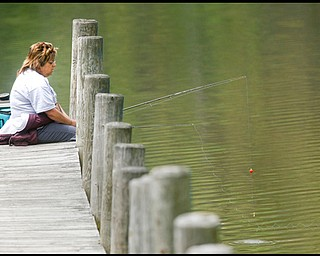 FISH FEEDER: Debbie D'Altorio of Boardman tries her hand at fishing off a pier in Lake Newport in Mill Creek Park. Although she enjoyed the setting and the milder weather, she said she wasn't having much luck, just feeding the fish with a hook.