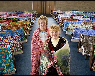 5.13.2009 Blankets take the seats of the congregation that made them as Diane Wise and Wanda Marland wear two of the 117 blankets made by their fellow members of Western Reserve United Methodist Church for delivery to Berea Children's Home and Sojourner House. The congregation spent about a month making the blankets that will be given to infants, children, teenagers and battered women.