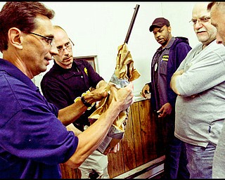 5.13.2009 Youngstown police officers inspect a rifle received during the Youngstown Gun Buy Back program at the downtown department.