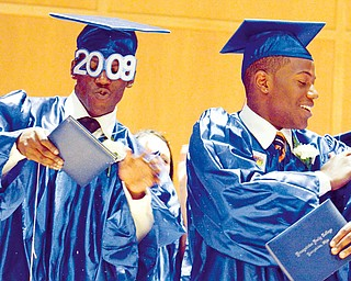Twin brothers James A. Davis III, left, and Justin A. Davis, right, both 18, brush off confetti and silly string during a celebration onstage for their graduation of Youngstown Early College. The Class of 2009 Commencement was held at DeYor Center, Wednesday May 20, 2009.
