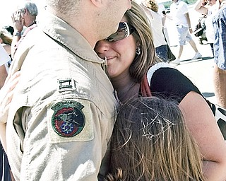 Justin Fadem, 29, of Howland hugs his step daughter, Zoe Neleach, 8, and his pregnant wife Brandi, 28. Justin just came back from a tour in Southeast Asia.