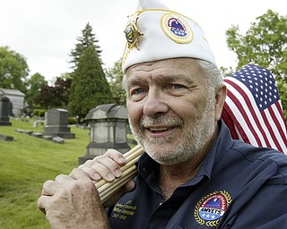JP Brown III, former national Amvets Cmdr. helps decorate graves in Youngstown's Oak Hill Cemetery.