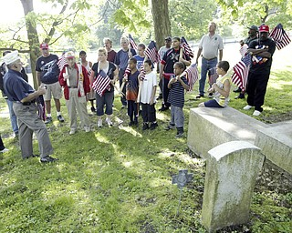 JP Brown III, left of Boardman, a  Navy veteran and former Amvets National Commander leads a brief ceremony at the grave of Maj. John A. Logan in Oak Hill Cemetery Sat May 16. Veternas groups and volunteers placed flags on graves at the cemetery.