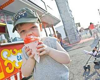 3-year-old Landon Joyce of Boardman bites into a cherry sno-cone at the Southern Park Mall Event of Bates Brothers Carnival, Friday May 22, 2009.
