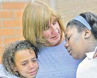 Carole Betz, Willard School Warren counselor, hugs 6th graders De'Shey Staggers, left, and Chaleesa Seawood during a Friday ceremony at the school. Fellow student Lloyd McCoy Jr.,  a 6th grader at the school, was killed in a recent shooting. May 22 was his birthday. Students planted a tree in his honor.