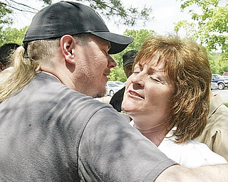 UAW members Molly Less of Berlin center and James Simlins of Boardman embrace outside Metroplex after vote Thursday.