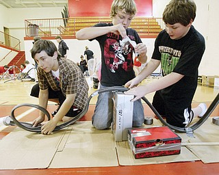 From left to right, Matthew Deal Dustin Thailing and Jesse New work on their coaster during roller coaster contest at Girard Junior High School. 7th graders participated in the event Friday.