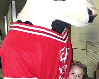 Allyson Andrews, Dobbins Elem School, Poland gets a hug from the Chik-Fil-A cow during a visit to the school Monday. Dobbins was one of 10 school sin the country to win Chik-Fil-A Core Essentials program.