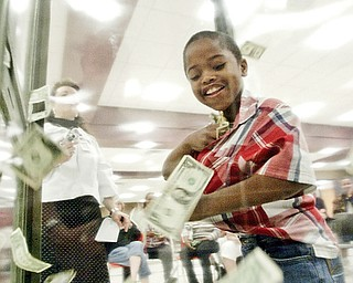 Zion Rushton, kindergarten student at Harding Elementary school stuffs cash into his shirt in the money machine during Friday event at Choffin Career Center. Students in the district with prefect attendance got a chance to grab cash in a money blowing machine.
