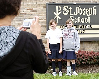 Nicole Strollo takes a photograph of her daughter Rachel, 11, and friend Maddie Sanders, 12, outside St. Joseph School for the last day, June 5 2009