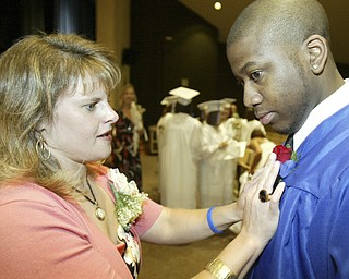 Poland HS Senior David Porch gets his corsage pinned on by teacher Stacy Benson before Sunday graduation.