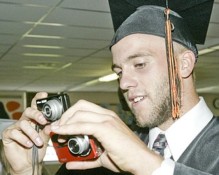 Two fisted photographer and 2009 Springfield HS grad Todd Kibby snaps photos of fellow grads during Sunday commencement.