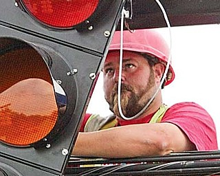 Bink Harter, an employee of Perram electric of Wadsworth, installs new traffic signal at Liberty and Hall avenues in Hubbard on June 8. New signals are being installed in the city.