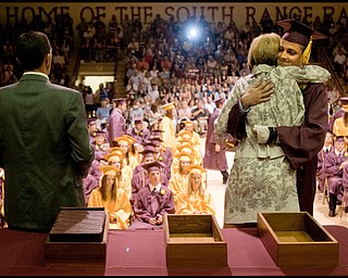 6.13.2009 Donald DeChellis hugs his mother, Delaine DeChellis, President of South Range Board of Education while on stage to receive his diploma during the South Range commencement ceremony in the school's gymnasium on Saturday afternoon.