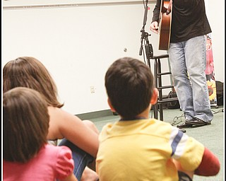 Abby Schindell (5) and her brother Joshua (6) of Hubbard sing along with other children and adults with Chip Richter as he performs in the Media Room at Hubbard Local Library on Monday June 15, 2009. Photo by: Lisa-Ann Ishihara