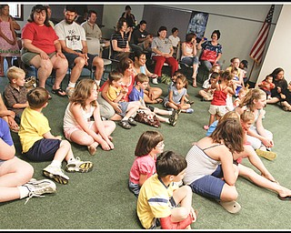 Children and adults sing along with Chip Richter as he performs in the Media Room at Hubbard Local Library Monday June 15, 2009 Photo by: Lisa-Ann Ishihara