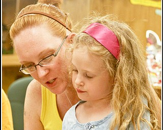 Camp Read: Rachel Scacchetti of Hubbard reads to her daughter Isabella (5) to pass time in the Hubbard Children's Library before they watch Chip Richter perform in the Media Room, Monday June 15, 2009 Photo by: Lisa-Ann Ishihara