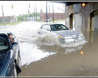 6.17.2009 Damon Washington (left), of Youngstown, sits in his car beneath the B&O Railroad bridge on Marshall St. in front of its intersection with Oak Hill Ave as another motorist passes him by braving the flooding water that left his car unable to start. After a passerby unsuccessfully tried to help jump the waterlogged car, Washington was able to reach family and friends on a cell phone and they were able to come and tow the car away where it could dry out. Photo by: Geoffrey Hauschild