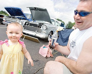 13 month old Kalli Stephens, of Ravenna, smiles after her taking a drink of her father, John Stephens', beverage during the annual Fathers Day Car Show at Springfield High School on Sunday afternoon. John's stepfather's 1955 Silver Cheverolet can be seen in the background and to the left of that sits John's 1967 Blue Ford Truck.