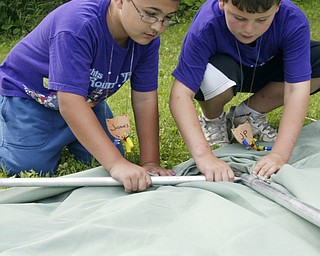 James Maruca, 9, left, and JP Yerian, 8, members of Cub Scout Pack 2 of Poland work at pitching a tent during Cub Scout Day Camp at Camp Stambaugh in Canfield Thursday. wd lewis