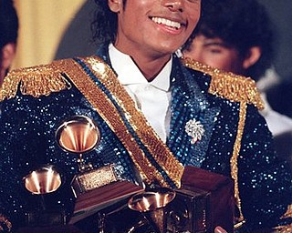 FILE - In this Feb. 28, 1984 file photo, Michael Jackson is seen backstage at the 26th annual Grammy Awards in Los Angeles as he poses with the awards he won in eight different categories. (AP Photo/Reed Saxon, file)