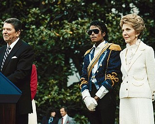 FILE - In this May 14, 1984, file photo, Michael Jackson , center, stands with President Ronald Reagan, left, and first lady Nancy Reagan  on the south lawn of the White House prior to receiving an award from the president for his contribution to the drunk driving awareness program. (AP Photo/Scott Stewart, file)