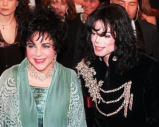 FILE - In this Feb. 16, 1998 file photo, actress Elizabeth Taylor arrives with pop singer Michael Jackson at the Pantages Theater in the Hollywood area of Los Angeles for a birthday celebration for Taylor. (AP Photo/Chris Pizzello, file)