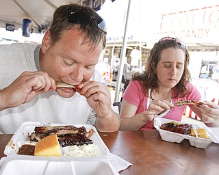 Michael Doran and Amy Padovano of Austintown chow down on ribs from Texas Pit BBQ at the Mahoning Valley Rib Burnoff Saturday June 27, 2009