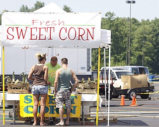 Christa Franklin (25) of Niles and Brandon Lucas (25) of Howland buy sweet corn from Lucas Cummins of Girard at the J & J Concession stand at the Mahoning Valley Rib Burnoff Saturday June 27, 2009