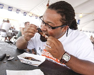 Laurence Haley (29) of Austintown indulges in ribs from Mojo's at the Mahoning Valley Rib Burnoff Saturday June 27, 2009