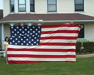 Sue, Katie and Mike Centorame of Canfield display the flag they inherited from their uncle and aunt, Steve and Doris Colucci of Youngstown. It hung over their front porch for the Bicentennial and appeared in The Vindicator at that time.
