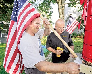 Kris Larson, left, and Peter Lopes attach an American flag to a soccer-themed Independence Day parade float in Bristol, R.I., Monday, June 30, 2009. Bristol residents have marked July 4th every year since 1785, allowing the town to lay claim to the nation's oldest Independence Day celebration.