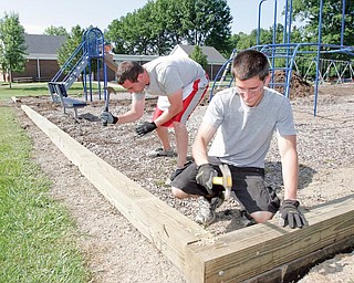 Lowe's Boardman store employees David Adkins, left, and Derrick Poppelriter volunteer to help refurbish a playground at Dobbins School in Poland.