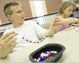 7.5.2009 Brandon Akuszewski, 11, creates a necklace while his sister, Lauren Akuszewski, age 8, both of Austintown, works on another red white and blue themed craft at Mill Creek MetroParks' Farm in Canfield on Sunday afternoon. Geoffrey Hauschild