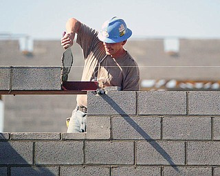 John Schreiber of Lencyk Masonry puts a brick and mortar in place at the South Range Schools facility being built on Route 46.