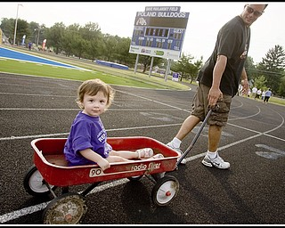 """7.10.2009 Gianna Bindas, 1, wears the purple shirt signifying a cancer survivor, while being pulled in a wagon by her father, Thomas Bindas, both of Poland, during the initial survivors lap of the Relay For Life at Poland's High School Stadium on Friday evening. Diagnosed at 9 months with a Wilms Tumor, Gianna has since had surgery, 21 weeks of chemotherapy, and despite loosing a kidney, her parents say she is """"doing real good."""" Geoffrey Hauschild"""